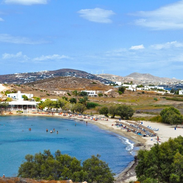 The crystal clear waters of the sea & the cove at Parasporos beach. Mountains of Paros in background