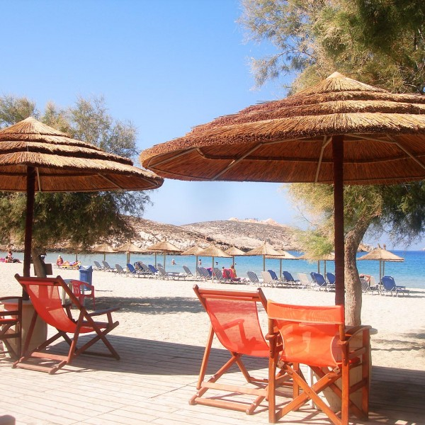 Deck chairs under rustic straw umbrellas. View of Parasporos beach, Aegean sea and Paros countryside