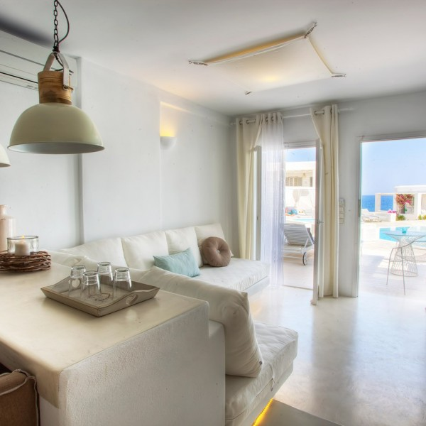 Corner sofa, lamps, & table with candle & glasses in Superior Ground Floor Pool View Suite, Paros.