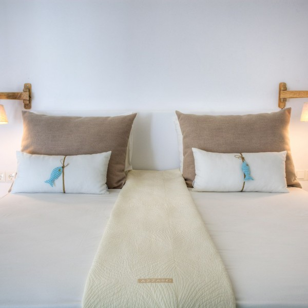 Lamps, bedsheets & pillows on bed in Minois Village Superior Ground Floor Pool View Suite, Paros