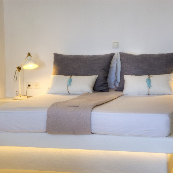 Bedside lamps, bed, pillows & sheets in Minois Village Superior Ground Floor Pool View Suite, Paros.