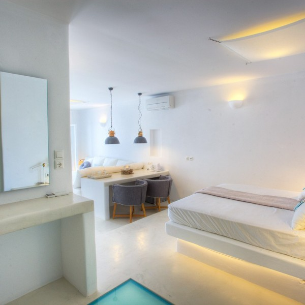 Mirror, table, double bed & lamp in Minois Village Superior Ground Floor Pool View Suite, Paros.