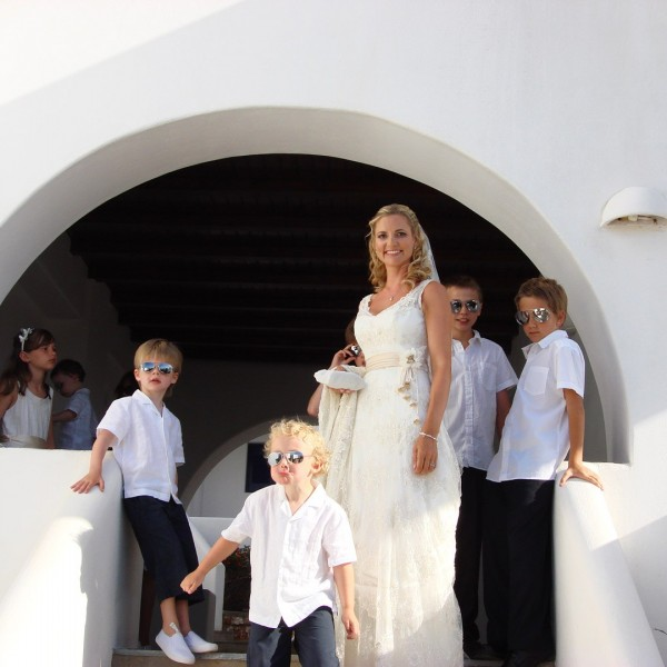 Blonde bride poses next to page boys wearing sunglasses during wedding at Minois Village in Paros.