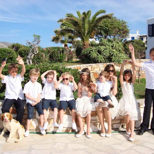 Children pose for photo with a dog in front of palm trees outside Minois Village Hotel Suites, Paros